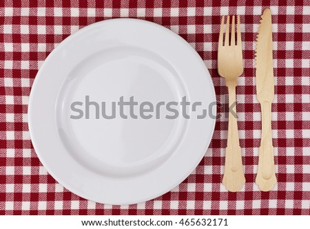 checkered tablecloth in red and white with wooden fork and knife and porcelain plate