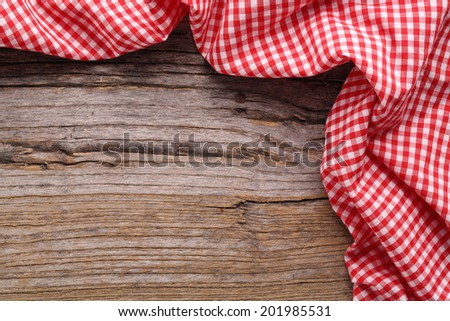 Checkered tablecloth on wooden table - stock photo