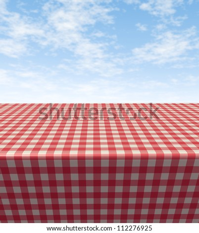 Checkered tablecloth table with a blank empty picnic cloth in perspective on a blue sunny summer sky as a symbol of food and leisure fun. - stock photo