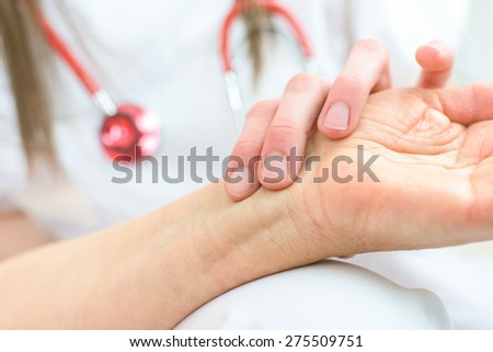 Checking a patient's pulse - stock photo