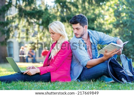 Checking a school assignment. Girl-student and male student holding a laptop and books and look at the camera while sitting on the grass near the campus of the University at the break. - stock photo