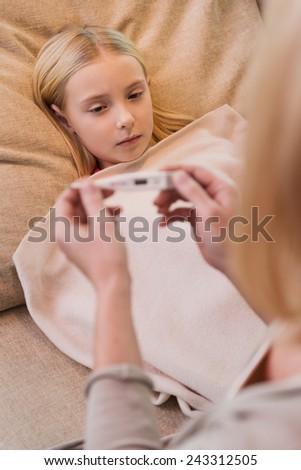 Checking body temperature. Mother looking at the thermometer while her ill daughter lying in bed covered with blanket  - stock photo