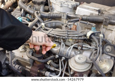 Checking engine oil dipstick in the car - stock photo