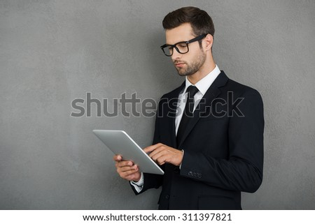 Checking his emails online. Serious young businessman working on his digital tablet while standing against grey background - stock photo