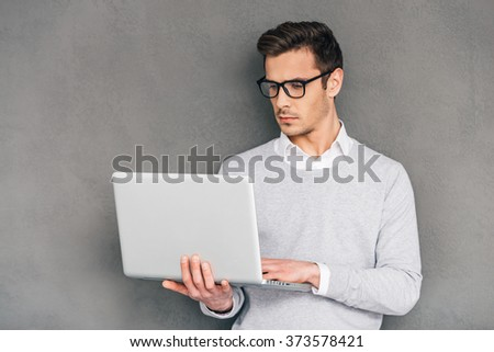 Checking his timetable. Confident young man holding laptop and typing while standing against grey background - stock photo