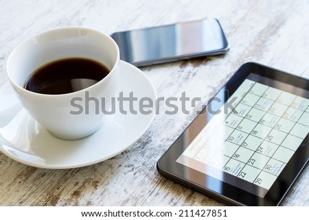 Checking monthly activities and appointments at the office in the tablet  - stock photo