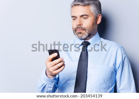Checking out business messages. Confident mature man in shirt and tie holding mobile phone and looking at it while standing against grey background