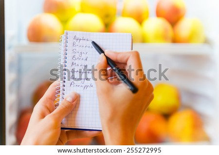 Checking shopping list. Close-up of woman checking shopping list with apples in the background   - stock photo