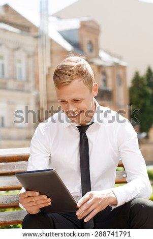 Checking social media. Young handsome smiling man sitting on bench and using tablet.