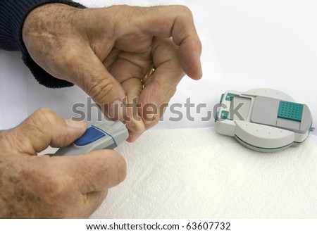 Checking sugar levels: closeup of diabetic senior male's hands while he is checking his sugar levels. - stock photo