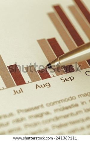 checking the annual sales chart with ballpoint pen - stock photo