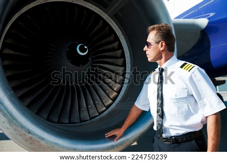 Checking the engine. Confident male pilot in uniform examining turbine engine of airplane   - stock photo