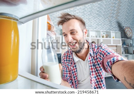 Checking the fridge. Young and successful male looks in the fridge and take out of the fridge a bottle of milk while standing in the kitchen and makes breakfast.