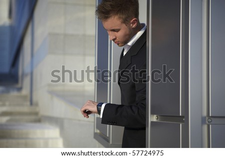 Checking the time. Worried young businessman