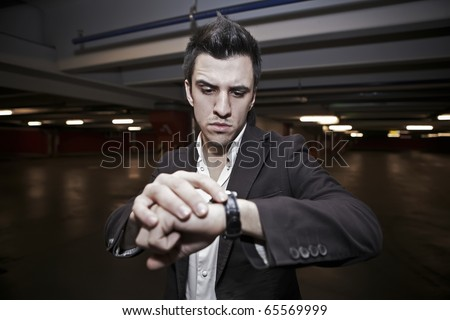 Checking the time. Worried young businessman - stock photo