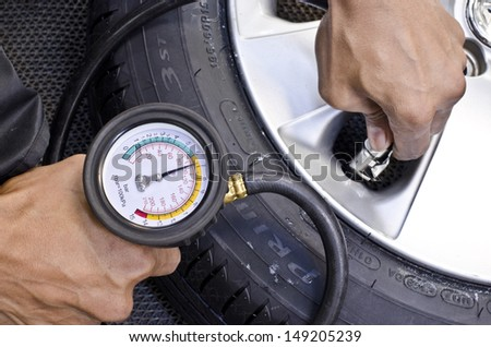 Checking tire pressure. Pumping air into auto wheel. Vehicle safe concept. - stock photo