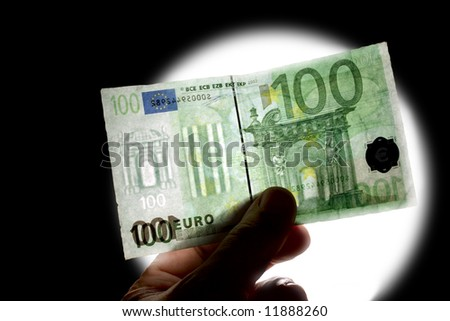 checking watermark 100 euro isolated on black with white lamp - stock photo