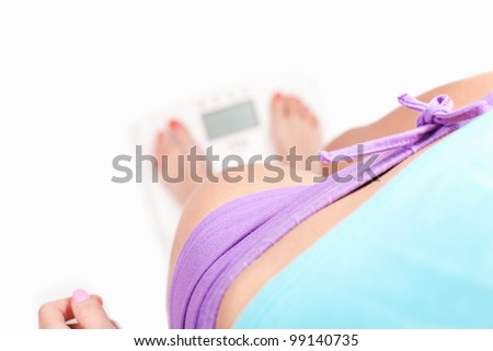 Checking weight, girl standing on digital scale - diet concept, on white background - stock photo