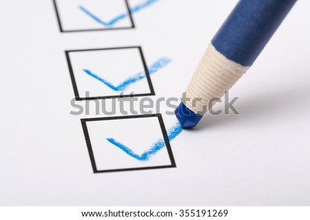 Checklist and pencil close-up on white background