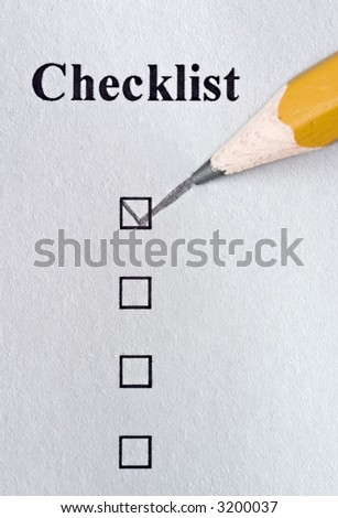 Checklist being filled out in pencil with texture showing in paper - stock photo