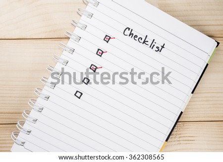 Checklist on notebook page with wood background