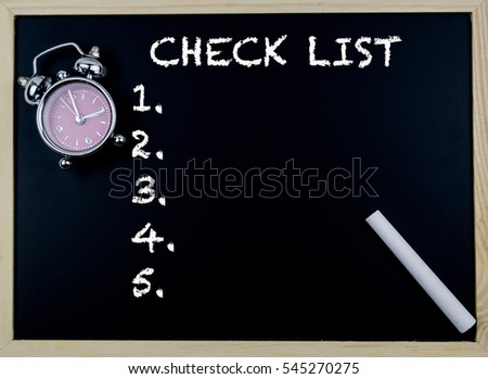 Checklist word with clock on table in front of chalkboard
