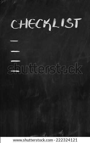 Checklist written with white chalk on blackboard - stock photo