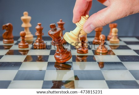 Checkmate! Winning at chess symbolized by knocking the opponent's king over.