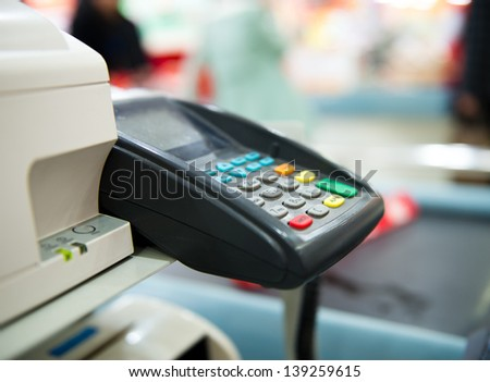 Checkout counter with terminal in supermarket. - stock photo