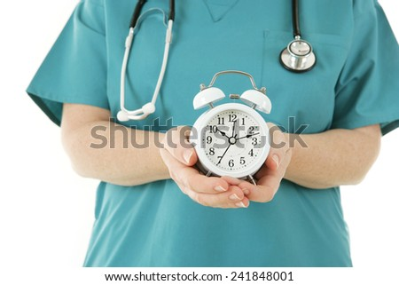 Checkup Time - Nurse holding an alarm clock - stock photo