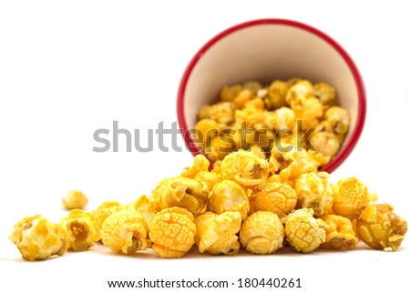 Cheddar and caramel popcorn mix spilled from red bucket isolated on white - stock photo