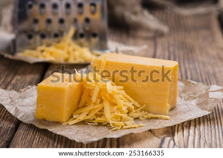 Cheddar Cheese (grated) as close-up shot on an old vintage wooden table - stock photo
