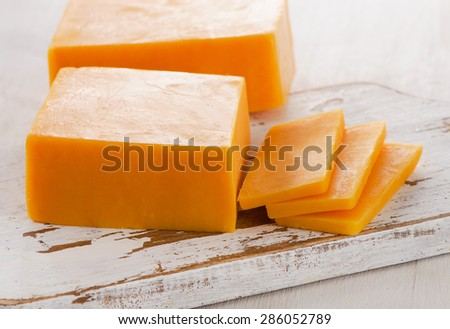 Cheddar Cheese on  white wooden Cutting Board. Selective focus - stock photo