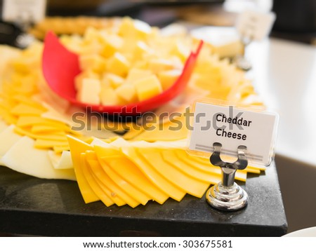 Cheddar Cheese Sign with Out of focus of cheese for background - stock photo
