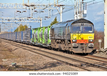 CHEDDINGTON, ENGLAND - JANUARY 19: A Tesco freight train heads southbound on January 19, 2012 at Cheddington. Tesco has introduced two new rail freight trains removing 40,000 road journeys per annum - stock photo
