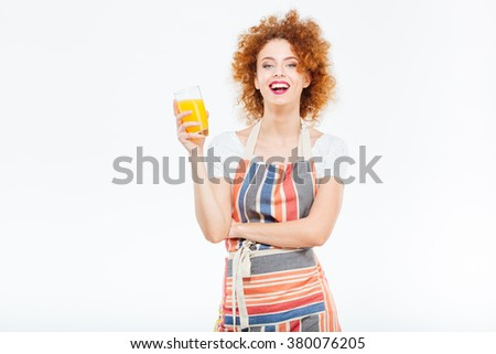 Cheeful beautiful young woman in striped apron laughing and holding glass of orange juice over white background - stock photo