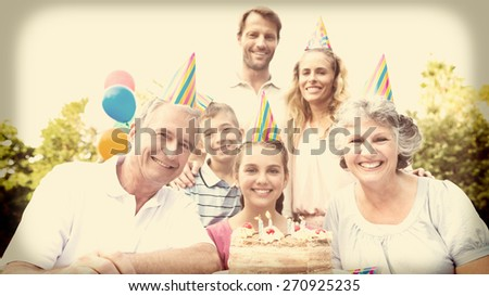 Cheeful family smiling at camera at birthday party outside at picnic table - stock photo