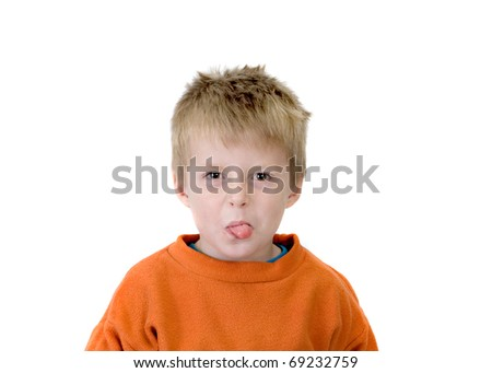 cheeky boy poking his tongue out. - stock photo