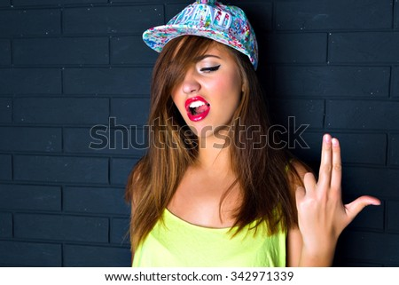 Cheeky bright fashion portrait of crazy funny girl imitating gun by her hand,  bright crop top and swag hat, black urban wall background.