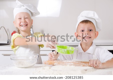 Cheeky happy little boy and girl wearing white chefs uniforms standing at a counter in the kitchen baking a batch of fresh biscuits - stock photo