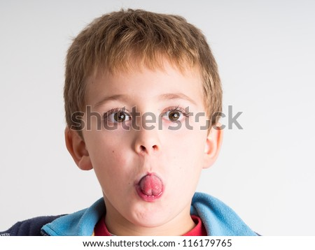 Cheeky kid making funny expressions - stock photo