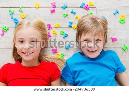 Cheeky kids. Top view of two cute little children looking at camera and smiling while lying on the floor with plastic colorful letters laying around them - stock photo
