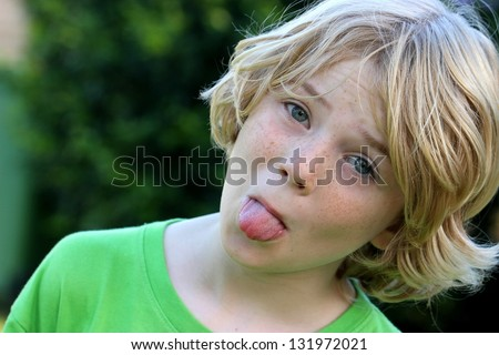 Cheeky naughty kid poking his tongue - stock photo