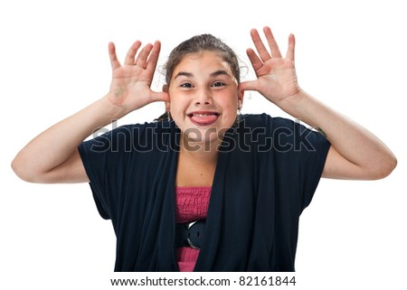 Cheeky teenage girl sticking out her tongue with the hands on the head, studio shot against a white background. - stock photo