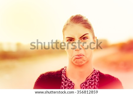 Cheeky woman mocking in a playful humorous joke.Negative human emotion facial expression.Young pretty woman with funny face mocking someone.Young pretty woman with funny face - stock photo