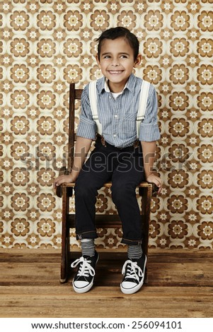 Cheeky young boy in braces sitting in studio - stock photo
