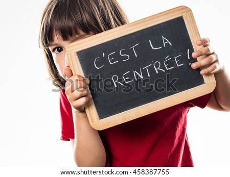 cheeky young kid hiding behind a French writing slate, informing about a scary back to school, white background studio