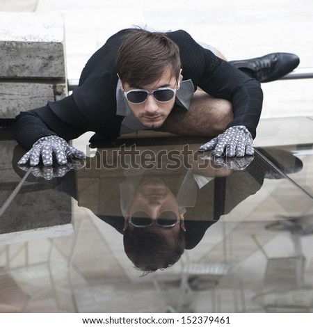 cheeky  young man in fashionable glasses near glass wall - stock photo