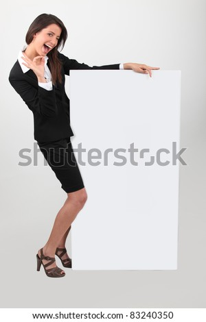 Cheeky young woman in skirt suit with blank board - stock photo