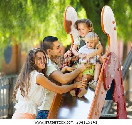 Cheerfu parents helping kids on slide in summer day - stock photo